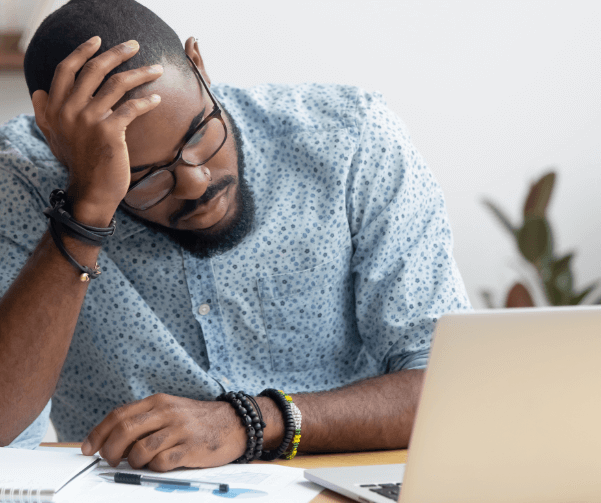 Frustrated man on computer on true cost of fraud