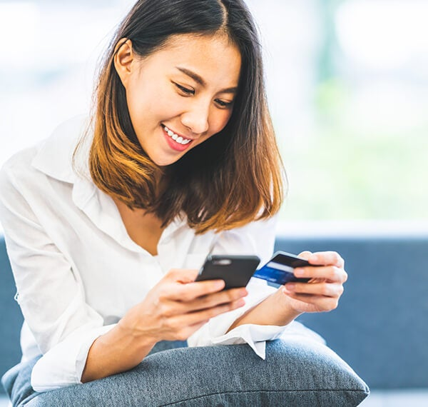 Woman looking at smart phone and credit card