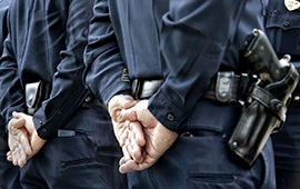 Officers standing with hands behind back