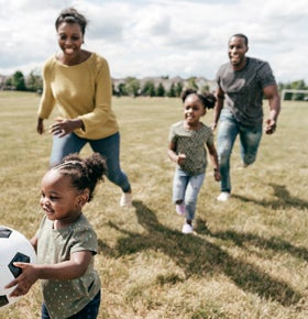 family with young children playing soccer