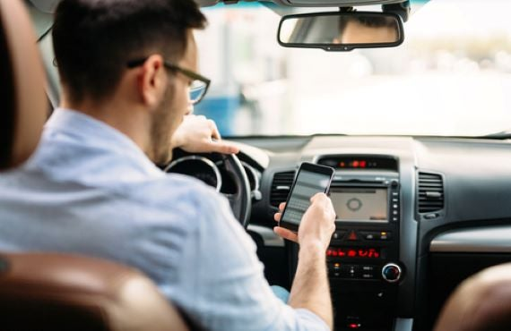 Automotive Digital Adoption man looking at phone in car